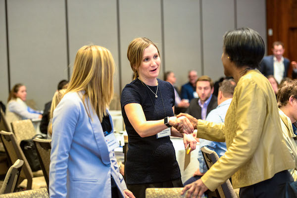 Two women shake hands over networking session.